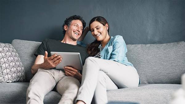 A couple using a digital tablet together while relaxing at home
